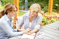 Healthcare at home. Home caregiver sitting at home in the garden with senior women and measuring blood pressure while explaining medicine dosage to patient Royalty Free Stock Photo