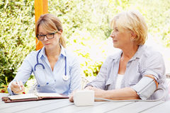 Healthcare at home. Home caregiver sitting at home in the garden with senior women and measuring blood pressure while explaining medicine dosage to patient Stock Photography