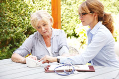 Healthcare at home. Home caregiver sitting at home in the garden with senior women and measuring blood pressure while explaining medicine dosage to patient Royalty Free Stock Images