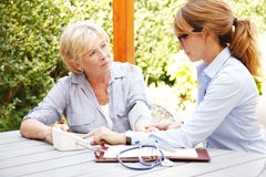 Healthcare at home. Home caregiver sitting at home in the garden with senior women and measuring blood pressure while explaining medicine dosage to patient Stock Images