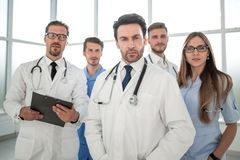 Young doctors looking at camera. Healthcare, hospital and medical concept - young team or group of doctors royalty free stock photos
