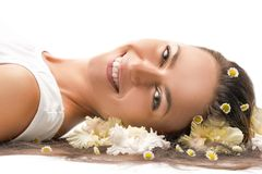 Healthcare Ideas. Portrait of Smiling Caucasian brunette Woman Laying on Floor and Having Hair with Flowers stock photos