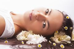 Healthcare Ideas. Portrait of Tranquil Caucasian brunette Woman Laying on Floor and Having Hair with Flowers royalty free stock images
