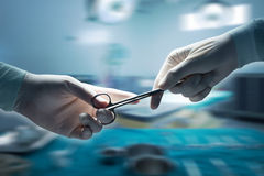 Healthcare and medical concept , Close-up of surgeons hands. Holding surgical scissors and passing surgical equipment , motion blur background Stock Photos