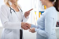 Healthcare and medical concept - doctor with patient in hospital. Handshake. Royalty Free Stock Image
