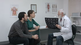 Healthcare and medical concept. Doctor with patients looking at x-ray. stock footage