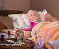 Sick old woman lying in bed at home Royalty Free Stock Images