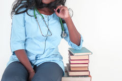 Healthcare and medical concept. Woman doctor sitting near a stack of books Stock Photos