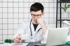 Healthcare, medical and pharmacy concept - male doctor with packs of pills stock images