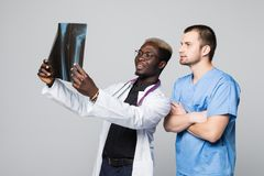 Healthcare, medical and radiology concept - two doctors looking at x-ray on gray background royalty free stock photography