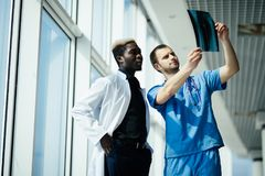 Healthcare, medical and radiology concept - two mixed race doctors looking at x-ray in modern hospital royalty free stock image