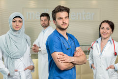 Healthcare and medicine concept - attractive male doctor in front of medical group in hospital showing thumbs up Royalty Free Stock Photo