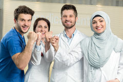 Healthcare and medicine concept - attractive male doctor in front of medical group in hospital showing thumbs up Stock Photos