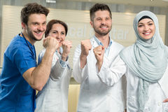 Healthcare and medicine concept - attractive male doctor in front of medical group in hospital showing thumbs up Stock Images