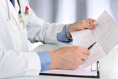 Healthcare and medicine concept -  doctor with clipboard analizing cardiogram Stock Photos