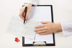 Healthcare and medicine concept - doctor with medical clipboard. And red pills analyzing cardiogram. Top view Stock Image