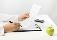 Healthcare and medicine concept - doctor with medical stethoscop. E and green apple analyzing cardiogram results Stock Photo