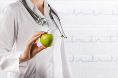 Healthcare and medicine concept - Female doctor's hand holding green apple. Close up shot on grey Stock Photography