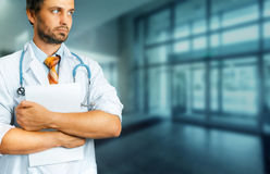 Healthcare And Medicine concept. Male Doctor with Medical Document Journal. Young Male Doctor In White Coat With A Stethoscope holds medical documents stock photo