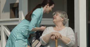 Healthcare Nurse fixing pillow fluffing to Old Woman Patient Smiling Happy Outdoors on Sunny Day at the Nursing Home shot on Red C. Amera stock footage