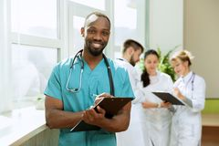 Healthcare people group. Professional doctors working in hospital office or clinic. Healthcare people group. Professional african american male doctor posing at stock image