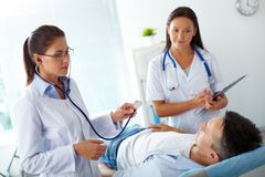 Healthcare. Portrait of two female doctors looking at patient during medical treatment in hospital Royalty Free Stock Photo