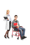 Healthcare practitioner pushing man in wheelchair Stock Photography