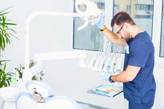 Healthcare, profession, stomatology and medicine concept -  male dentist  over medical office background Royalty Free Stock Photo