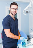 Healthcare, profession, stomatology and medicine concept - smiling male  dentist over medical office background Stock Photography
