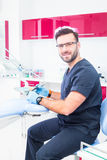 Healthcare, profession, stomatology and medicine concept - smiling male dentist  over medical office background Stock Photos