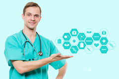 Healthcare, profession, symbols, people and medicine concept - smiling male doctor  in coat over blue background with Stock Photography