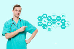 Healthcare, profession, symbols, people and medicine concept - smiling male doctor  in coat over blue background with Royalty Free Stock Images