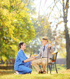 Healthcare professional helping senior man sitting outside Stock Photography