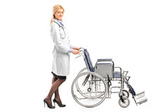 Healthcare professional pushing a wheelchair Stock Photos