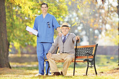 Healthcare professional standing next to a senior man seated on Stock Photo