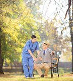 Healthcare professional talking senior man seated on bench outsi Stock Photography