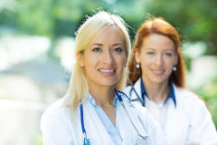 Healthcare professionals. Closeup portrait headshot happy, smiling female doctors, healthcare professionals isolated outdoors hospital background. Patient visit stock image
