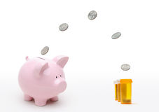 Healthcare Reform. Concept. Coins flying from piggy bank to fill pill bottles. Savings, spending, medical cost and spending Stock Photos