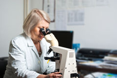 Healthcare researcher looking through a microscope Royalty Free Stock Photography