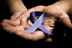 Mans hands holding purple domestic violence awareness ribbon. Healthcare and social problems concept - mans hands holding purple domestic violence awareness Royalty Free Stock Photo
