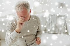 Senior man suffering from headache at home. Healthcare, stress and people concept - tired senior man suffering from headache at home over snow Stock Image