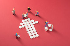 Healthcare system growth. Working men building an arrow made of pills, symbol for social growth Stock Photo