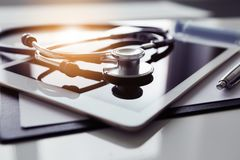 Tablet and stethoscope on white table stock images