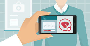 Healthcare and technology. Doctor visiting a patient at the hospital, he is using an augmented reality app and monitoring heartbeat, healthcare and technology Royalty Free Stock Photo