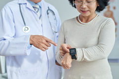 Healthcare Technology for Senior Patient. Close-up shot of middle-aged cardiologist standing next to his senior patient and showing her how to use fitness Stock Photos