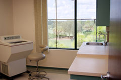Healthcare testing room. View inside doctor's room with machine, stool, sink, and counter Royalty Free Stock Photography