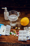 Healthcare, traditional medicine and flu concept - drugs, thermometer, honey and cup of tea on wooden table Stock Images