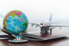 Healthcare and travel insurance concept. Stethoscope , passport document, airplane and globe royalty free stock photos