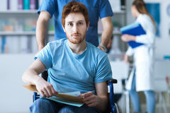 Healthcare worker pushing a man in wheelchair. Disabled young men in wheelchair checking his medical records, a male nurse is pushing him, illness and healthcare Stock Images
