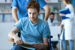 Healthcare worker pushing a man in wheelchair. Disabled young men in wheelchair checking his medical records, a male nurse is pushing him, illness and healthcare Stock Image